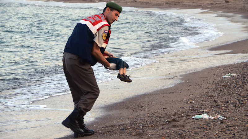 A paramilitary police officer carries the lifeless body of Aylan Kurdi. (AP Photo/DHA)